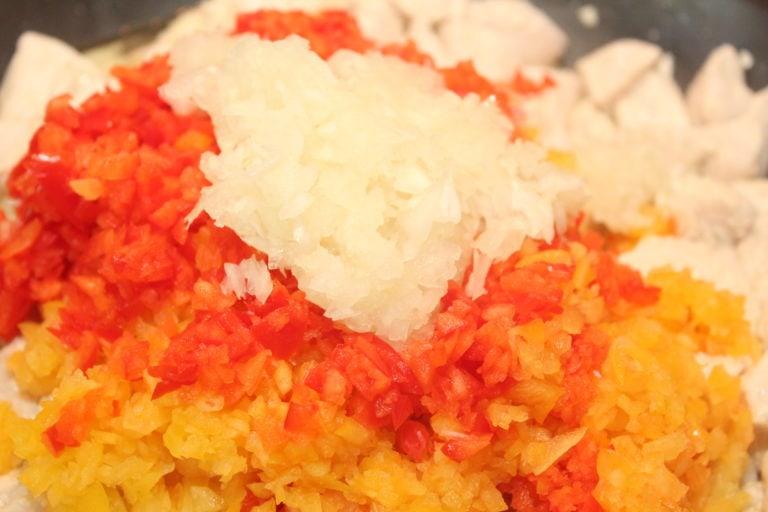 Gebe zu den angebratenen Hähnchenbrustfilets die rote und gelbe Paprika sowie zerkleinerte Zwiebel